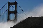 The fog rushes up a hillside framing the Golden Gate Bridge.
