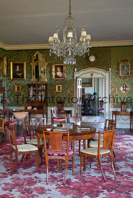The floor of the drawing room is covered with a bold carpet patterned with pink roses