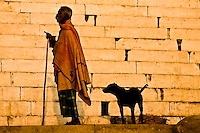 Old man holding walking stick and a black dog behind him on a ghat in Varanasi, Uttar Pradesh India. (Photo by Matt Considine - Images of Asia Collection)