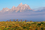 A buckrail fence dots the horizon line below the cloud covered Tetons in Grand Teton National Park.
