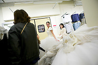 "Brides-to-be try on discounted wedding dresses with assistance from friends and family during the annual ""Running of the Brides"", a a first-come-first-served bridal gown sale, at the Filene's Basement store in New York City, USA, 3 March 2006."