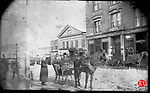 Frederick Stone negative. Front of 65  Bank Street, John Mullings &amp; Co. store in background.<br /> March 3,1888.