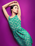 Young beautiful woman wearing vintage style green dress on purple background. Fashion photo.