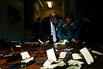 New Jersey, United States. 15th February 2013 -- NJ's Attorney General Jeffrey S. Chiesa and a police officer check weapons on a table after being acquired during the Gun Buyback program in New Jersey. Photo by Eduardo Munoz Alvarez / VIEWpress.