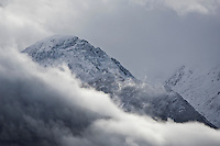 Mountain peak covered in fresh snow during summer storm, Glenorchy, New Zealand