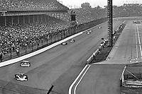 INDIANAPOLIS, IN - MAY 29: Al Unser leads a group of cars into Turn 1 in his Parnelli VPJ6B 001/Cosworth TC during the Indianapolis 500 on May 29, 1977, at the Indianapolis Motor Speedway in Indianapolis, Indiana.