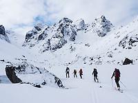 Skiløpere på topptur på vei opp Sørfjorddalen mot Øksfjordjøkelen. Oppgang til breen til venstre i bildet. ---- Skiers on their way from Nuvsvåg towards Øksfjordjøkelen.