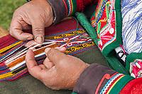 Quechua woman works a loom used to make textiles, Cusco Peru, South America