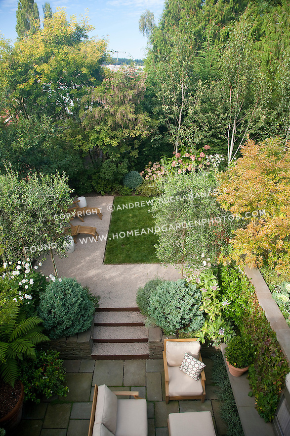 An overhead view of the lower fireplace area and the middle lawn area in this multi-level Seattle backyard.