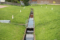 One of the many Concrete lined drains that channel water back into the sea away from houses, Canvey Island, Essex, Britain - Jun 2014.