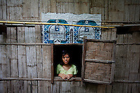 """Zune Nwe Tun Oo, 17 year old refugee from Mandalay in Myanmar looks through the window of her home at the Mae La refugee camp near Mae Sot June 3, 2012. Asked about Aung San Suu Kyi's visit to the camp Zune Nwe Tun Oo said """"She is my inspiration. I spoke to her yesterday briefly and now I changed my mind - before I wanted to go to third country, get education and have a big house. Now, I want to come back after my education. I want to go back. My people need me."""" Myanmar's pro-democracy leader Aung San Suu Kyi visited on Saturday Mae La, the biggest refugee camp along the Thailand-Myanmar border where tens of thousands of her compatriots found shelter after escaping from Myanmar.  REUTERS/Damir Sagolj (THAILAND)"""
