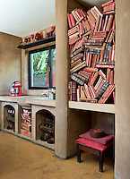 Antique books are stowed higgledy-piggledy in a bookshelf in the kitchen