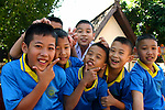 Thai Schoolboys mugging and smiling for the camera. Schools are often found within temple compounds in Thailand, and in fact are local centers of each neighborhood serving as a kind of &quot;community center&quot;.