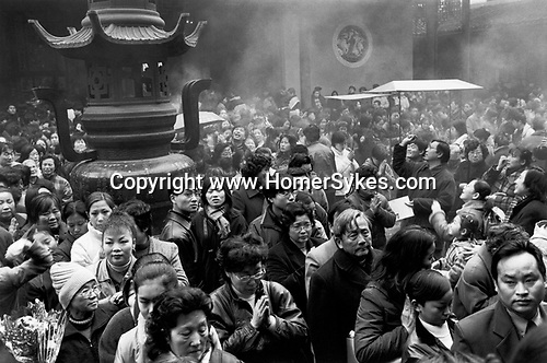 China, Shanghai.  The Jade Buddha Temple during the Spring Festival, or Chinese New Year as it is known in the West.  The diversity of Shanghais population can be seen in the faces of those crowding into the Temple.  According to the 2001 Census there are 54 ethnic groups in the municipality.....
