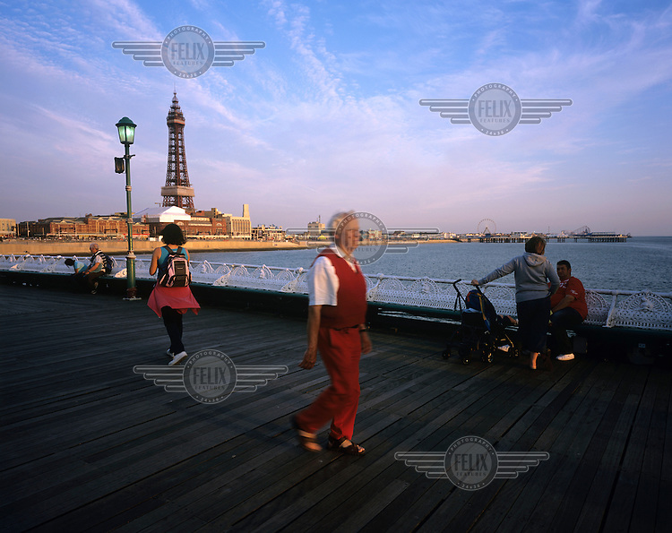 People walk on North Pier with Blackpool Tower in the distance at sunset in Blackpool.