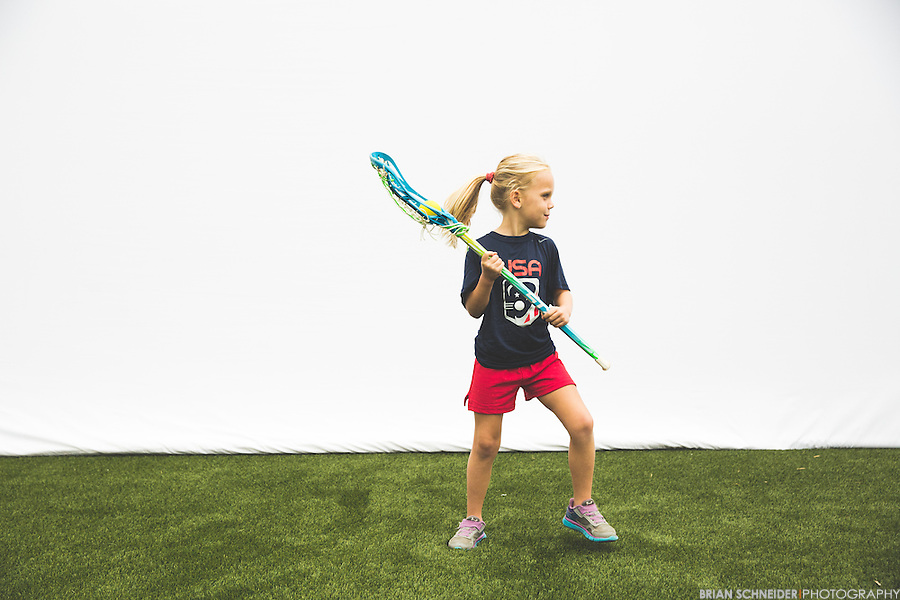 A 5 year old girl makes a lacrosse pass.