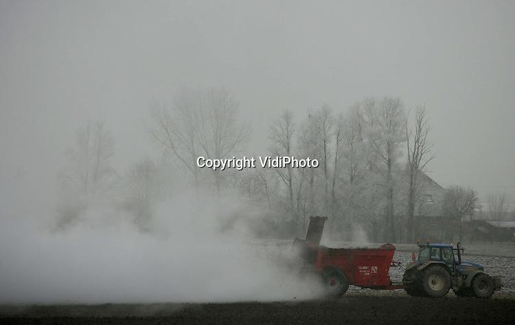 Foto: VidiPhoto..VALBURG - Warme mest op koude zorgt voor een enorme stoomwolk boven de akker van veehouder Erik Timmermans uit Valburg. De agrariër rijdt de vaste en warme mest uit en werkt die er, zoals verplicht, direct onder.