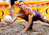 Competitor dives to dig up a spike during Toronto Beach Volleyball tournament.<br />