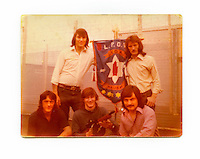 A photograph of loyalist prisoners holding up an Ulster Defence Association (UDA) pennant inside the Maze prison around 1977. The Maze prison, on the site of a former Royal Airforce station of Long Kesh on the outskirts of Lisburn in Northern Ireland was used during the Troubles (a period of intercommunal violence and strife which lasted for approximately 3 decades from the 1960s to 1998, when the Good Friday Agreement ended outright hostilities) to house paramilitary prisoners. It was closed in 2000 and partly demolished. The reverse of the photo reads: 'Hi Wes, Tell all the boys Sam and I were asking. See you in May. Sam will see you in June. Eric.'.