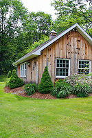 Large wooden Shed building office with evergreen foundation plants and hemerocallis daylilies, mulched garden beds, trees, lawn grass, landscaping