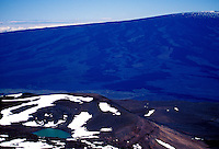 The snow dusted summit of Mauna Loa towers in the background of Waiau Lake on Mauna Kea on the Big Island of Hawaii.