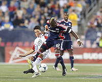 New England Revolution forward Dimitry Imbongo (92) attempts to control the ball as D.C. United midfielder John Thorrington (8) pressures. In a Major League Soccer (MLS) match, the New England Revolution (blue) defeated D.C. United (white), 2-1, at Gillette Stadium on September 21, 2013.