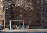 Travelers wait at a bus stop outside the NYCHA Elliot Houses complex of apartments in Chelsea in New York, seen on Saturday, March 30, 2013. The city has announced that it will be building affordable housing on underused land controlled by the housing authority.  (© Richard B. Levine)