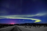 Aurora borealis swirls across the sky over interior Alaska and the James Dalton Highway. Lights from the Trans Alaska Oil Pipeline Pump Station glow in the distance.