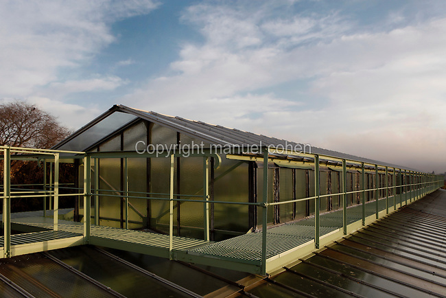 Roof of the Tropical Rainforest Glasshouse (formerly Le Jardin d'Hiver or Winter Gardens), 1936, René Berger, Jardin des Plantes, Museum National d'Histoire Naturelle, Paris, France. Oblique view showing walkways around the metal and glass roof structure beneath a cloudy sky.