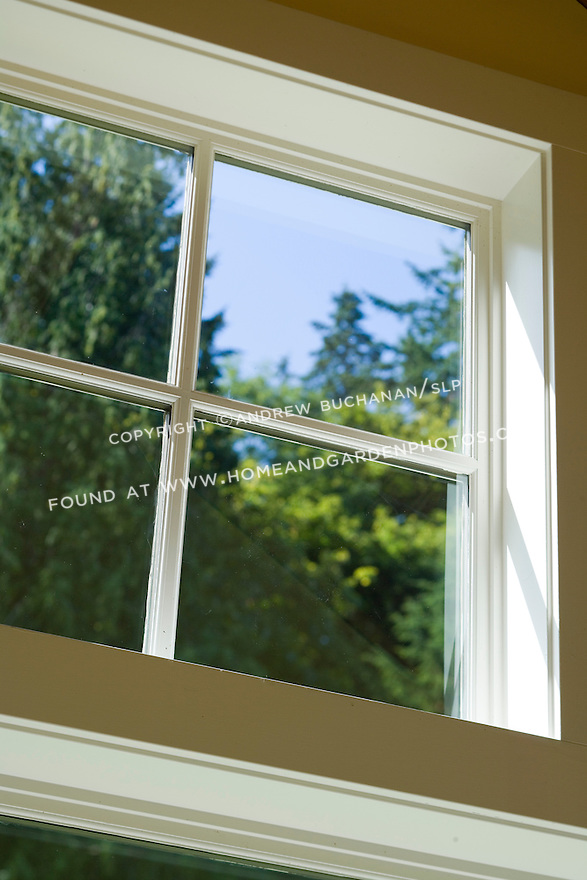 Close-up detail of a white-painted, 4-square, mullioned window with natural light casting in and tall evergreen trees in soft focus behind, in this waterfront weekend vacation retreat on Washington State's Vashon Island.