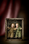 Two vintage dolls in a wooden box on a stage