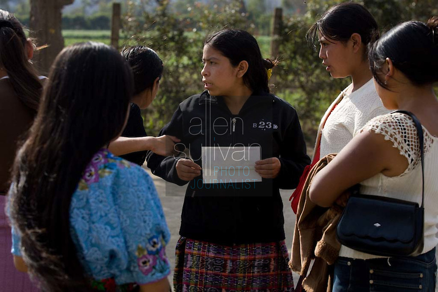Workers look over their paychecks during a shift change at Legumex, a vegetable and fruit company that exports to the United States, in Chimaltenango, Guatemala on Thursday, March 8, 2007. Shifts can run from 12 to 14 hours.