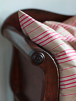 A striped cushion softens the turned arm of the sofa in the kitchen/dining area