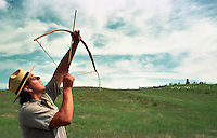 Ranger Michael Marshall, himself a Lakota Sioux Indian, fires off an arrow on the Little Bighorn Battlefield following a demonstration he gave to visitors on the arms and tactics of the 1876 battle. At right rear is Last Stand Hill where Lt. Colonel George Armstrong Custer met his notorious end. Two of Marshall's great grandfathers, named White Feather Tail and Bear, fought against Custer's troops at the Little Bighorn.