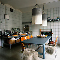 The kitchen dining room area was converted from a butcher's shop and still has the original wall tiles. The use of various shades of grey and blue soften the industrial feel of the room