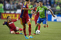 Clint Dempsey, right, of the Seattle Sounders FC dribbles the ball past a sliding Ned Grabavoy of Real Salt Lake during play at CenturyLink Field in Seattle Friday September 13, 2013. The Sounders won the match 2-0.