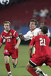 12 December 2008: Jason Herrick (center) of Maryland battles Anthony Vazquez (21) of St. John's for a loose ball.  The University of Maryland Terrapins defeated the St. John's University Red Storm 1-0 during the second sudden death overtime at Pizza Hut Park in Frisco, TX in an NCAA Division I Men's College Cup semifinal game.