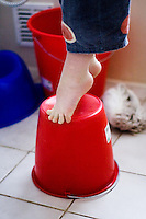 Toddler standing on his toes on a reversed red bucket on a white tiled bathroom floor.