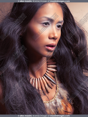 Ethnic beauty portrait of a young exotic woman with long beautiful hair wearing wooden necklace