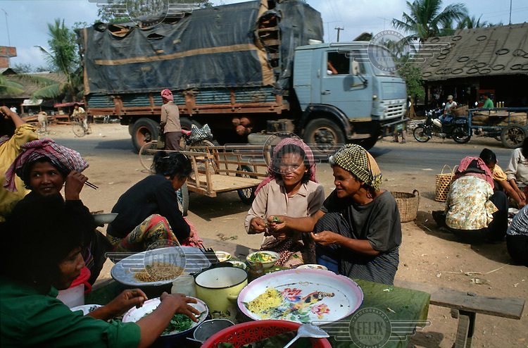 Busy food stall in a village strung along a major highway.