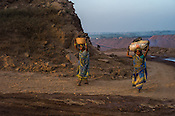 Scavengers carry coal from the open cast mine in Bokapahari village in Jharia, outside of Dhanbad in Jharkhand, India.  Photo: Sanjit Das/Panos