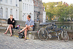 Cyclists sitting on a bridge in Bruges, Belgium, Europe