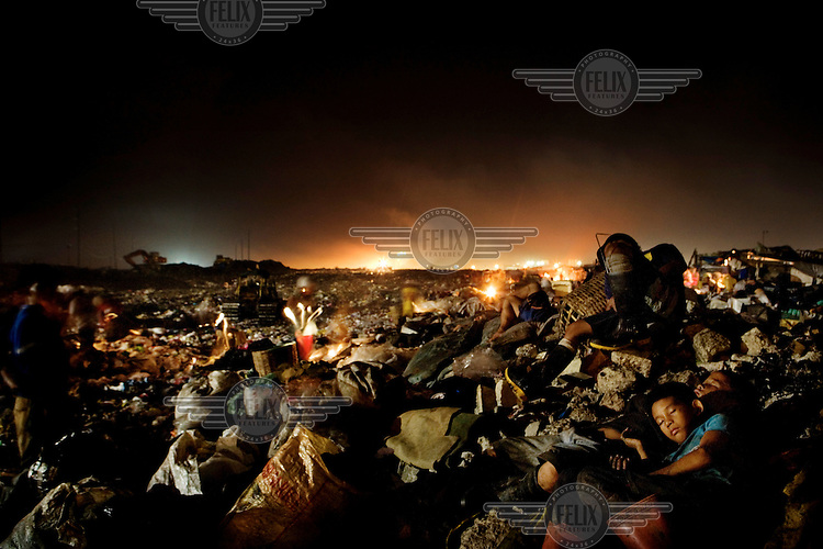 Two boys sleep in the city's toxic rubbish dump. The dump provides food and shelter for many homeless people. ..