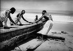 Fishermen taking a beached pirogue dugout canoe out to sea, Cote D'Ivoire.