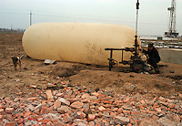Farmers steal natural gas from the Sinopec Petrochemical oil field in Puyang, Henan province, China in large plastic bags. Farmers in the area often steal natural gas for cooking and heating. They steal the gas from the pipe-line filling a big plastic bag in an hour. As soon as one finishes filling a bag, another family will fill another bag, it goes on continuously. A bag of natural gas is enough fuel for up to one week...PHOTO BY HI SHE / SINOPIX