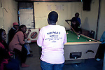CAPE TOWN, SOUTH AFRICA - OCTOBER 19: Zikona Moloyinyan wears a T-shirt  plays pool in a gay only bar on October 19, 2011 in Khayelitsha outside Cape Town, South Africa. Cape Town is a city known for tolerating gays and lesbians except in the townships where they get harassed and often attacked. Some women have been raped in so called corrective rape, where men rapes them to make them women again. They can't show their love freely on the streets in the townships so they usually have to meet in houses and this bar.  (Photo by Per-Anders Pettersson)