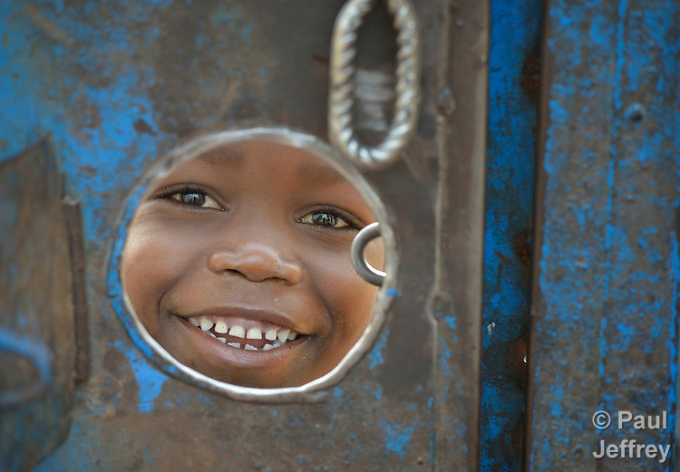 A peers through a hole in the gate around a church compound in the middle of a camp for for than 5,000 displaced people in Riimenze, in South Sudan's Gbudwe State, what was formerly Western Equatoria. Families here were displaced at the beginning of 2017, as fighting between government soldiers and rebels escalated.<br /> <br /> Two Catholic groups, Caritas Austria and Solidarity with South Sudan, have played key roles in assuring that the displaced families here have food, shelter and water.<br /> The camp formed around the Catholic Church in Riimenze as people fled violence in nearby villages for what they perceived as the safety offered by the church.