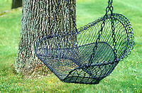 A swing with a metal seat is strung between two trees in the garden
