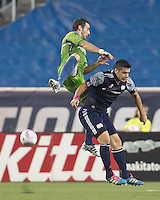 Seattle Sounders defender Zach Scott (20) and New England Revolution forward Milton Caraglio (9) battle for head ball. In a Major League Soccer (MLS) match, the Seattle Sounders FC defeated the New England Revolution, 2-1, at Gillette Stadium on October 1, 2011.