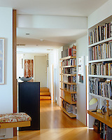 Bespoke bookshelves in this corridor work within the strict architectural lines of the interior